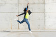 Woman with blue headphones listening music, jumping in the air