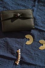 Black Purse With A Bow On A Blue Linen Background. Gold Jewelry, Earrings And A Pearl Barrette Next To The Wallet.