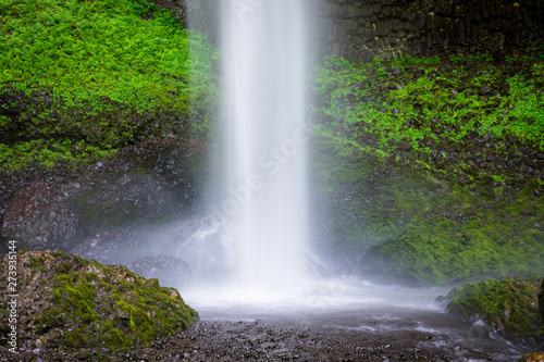 A beautiful waterfall splashing into a pool beneath rocks covered in lush green moss and vegetation - Latourell Falls in Oregon's Columbia River Gorge