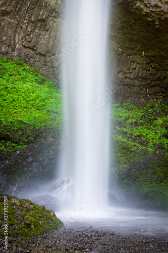 A beautiful waterfall splashing into a pool below a cliff covered in lush green moss and vegetation - Latourell Falls in Oregon's Columbia River Gorge
