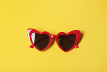 Stylish Heart Shaped Glasses On Color Background, Top View