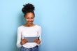Smiling mulatto woman standing with ipad looking at the screen and happily smile