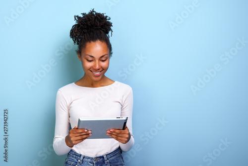 Photo  Smiling mulatto woman standing with ipad looking at the screen and happily smile
