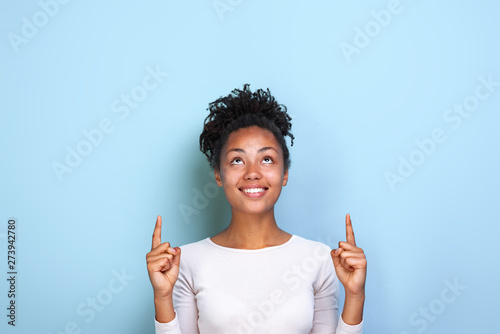 Obraz na plátně  Attractive mulatto woman pointing by her both index fingers up to place for copy