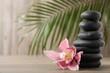 Stack of black spa stones with flower on wooden background. Space for text