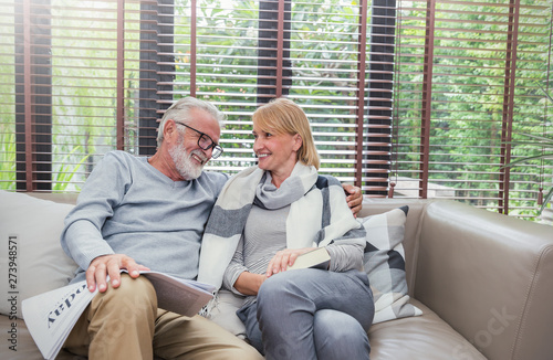Photo Portrait of happy old couple smiling in living room at home, caucasian senior couple relax in sofa