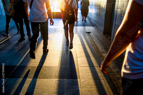 Fotografiet  Silhouettes of people walking in a dark tunnel against a white glow