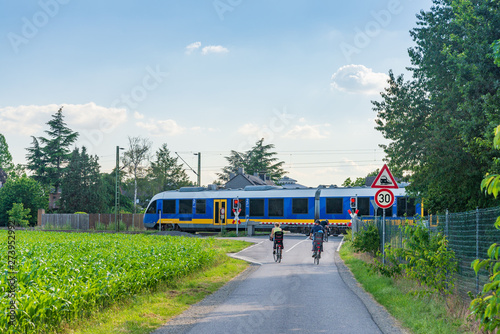 Outdoor sunny view of cyclists stop in front of level crossing railway barrier waiting for a train and green traffic light in small village countryside in Germany Canvas-taulu
