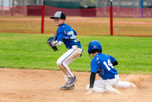 Youth Baseball Player In Blue Uniform Playing Short Stop Avoiding The Sliding Base Runner And Preparing To Throw The Ball.