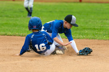 Youth Baseball Player In Blue Uniform Playing Short Stop Withstanding Base Runner Sliding Into The Base In A Cloud Of Dust.