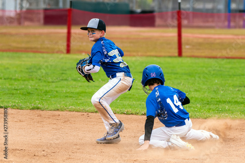Fotomural  Youth baseball player in blue uniform playing short stop avoiding the sliding base runner and preparing to throw the ball