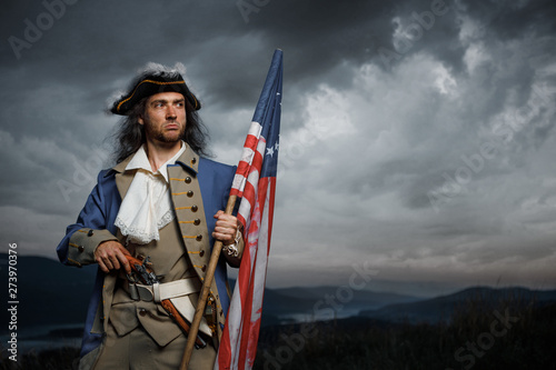 Soldier of United States War of Independence with flag and pistol posing over dramatic sky Canvas Print
