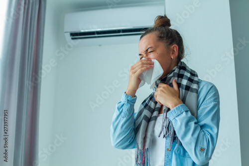 Fotografia  Sneezing woman caught a cold from the air conditioner at home