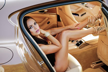 Concept Of Marketing And Advertising Exclusive Car. Sexy Girl In Golden Heels Posing In A Luxurious Vehicle In First Class Including Leather Seats.