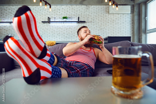 Fotografie, Obraz  Thick funny man eating a burger sitting on the couch.