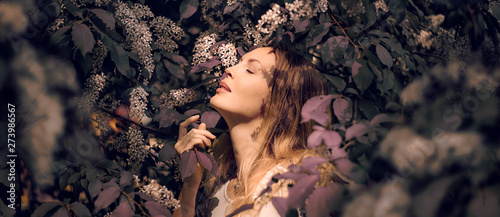 Pinturas sobre lienzo  lose up Portrait of a beautiful girl among spring foliage and flowers