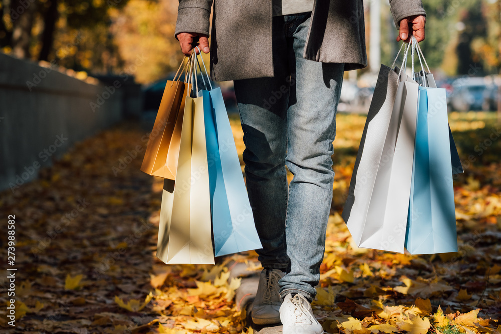 Fototapety, obrazy: Autumn shopping. Cropped shot of man walking with bags along sidewalk covered with yellow leaves. Fall background.