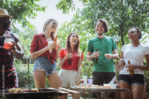 Foto  Group of happy friends standing eating and drinking beers at barbecue dinner cam