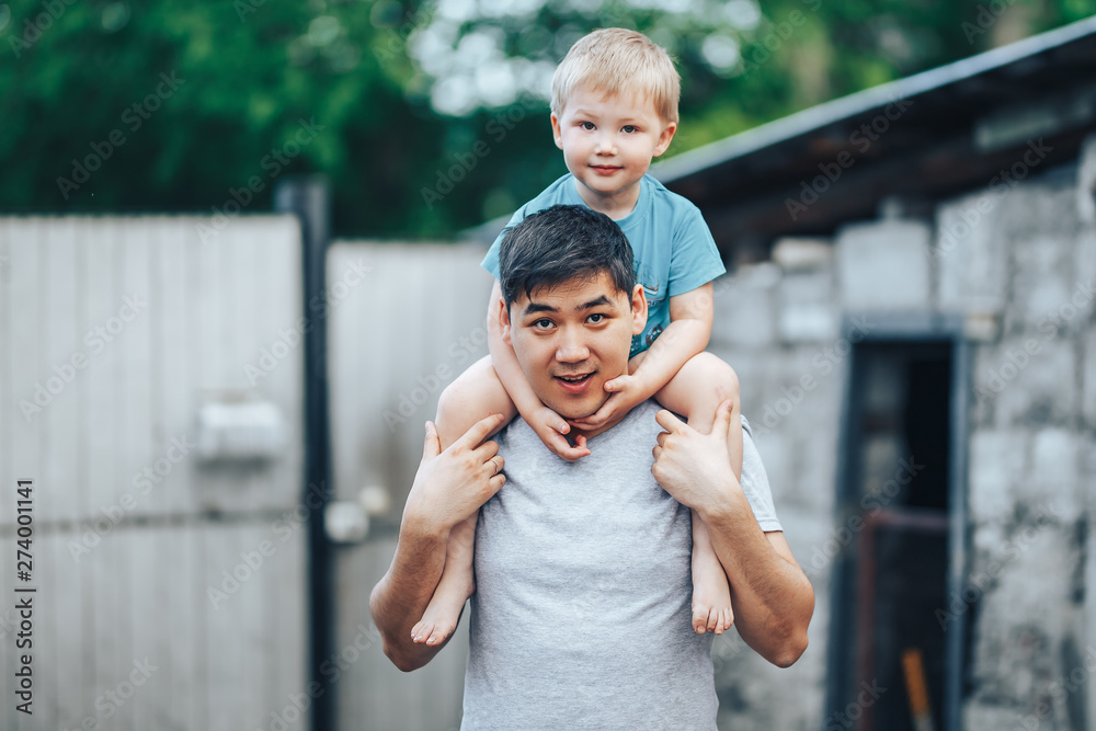 Fototapety, obrazy: blonde three years old boy sitting on father's shoulders. Kazakh father and caucasian mother. Happy father with black hair play with his caucasian son