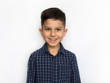 Portrait Of A Cute Little Smiling Boy In A Blue Shirt, Isolated On A White Background