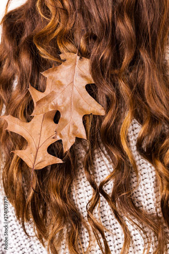 Woman with autumn leaves in long brown hair