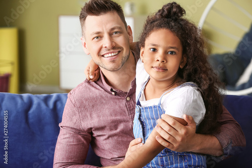 Happy man with little adopted African-American girl at home Canvas Print