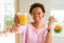 Young African American Woman Driking Orange Juice At Home Screaming Proud And Celebrating Victory And Success Very Excited, Cheering Emotion