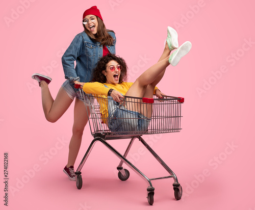 obraz dibond Cheerful young woman pushing shopping cart with friend