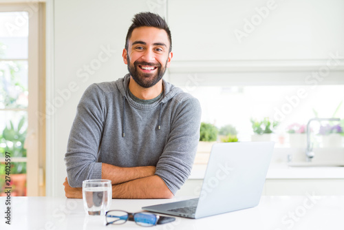 Cuadros en Lienzo Handsome hispanic man working using computer laptop happy face smiling with crossed arms looking at the camera