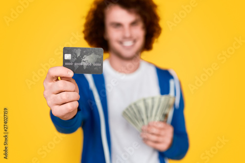 Blurred guy with money demonstrating credit card - 274027159