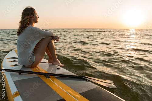 Spoed Foto op Canvas Ontspanning Beautiful young woman sitting on a stand up paddle board