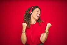 Middle Age Senior Woman Wearing Headphones Listening To Music Over Red Isolated Background Very Happy And Excited Doing Winner Gesture With Arms Raised, Smiling And Screaming For Success. Celebration