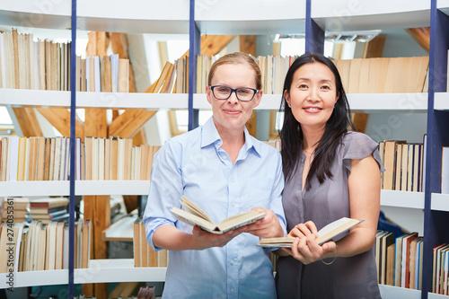 Photo Zwei Frauen mit Buch als Leser in der Bibliothek