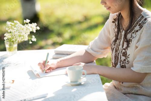 Leinwand Poster 自然の中で手紙を書く女性