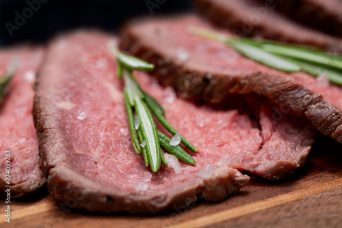 Sliced Grass Fed juicy Corn Roast Beef garnished with Rosemary Fresh Herb on natural wood cutting board. - 274039763