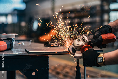 Obraz Grinding metal part at factory workshop, close-up. - fototapety do salonu