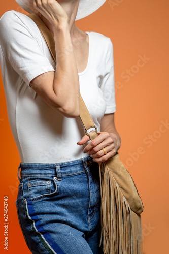 Spring summer casual female outfit with cross body bag, white shirt and waist jeans