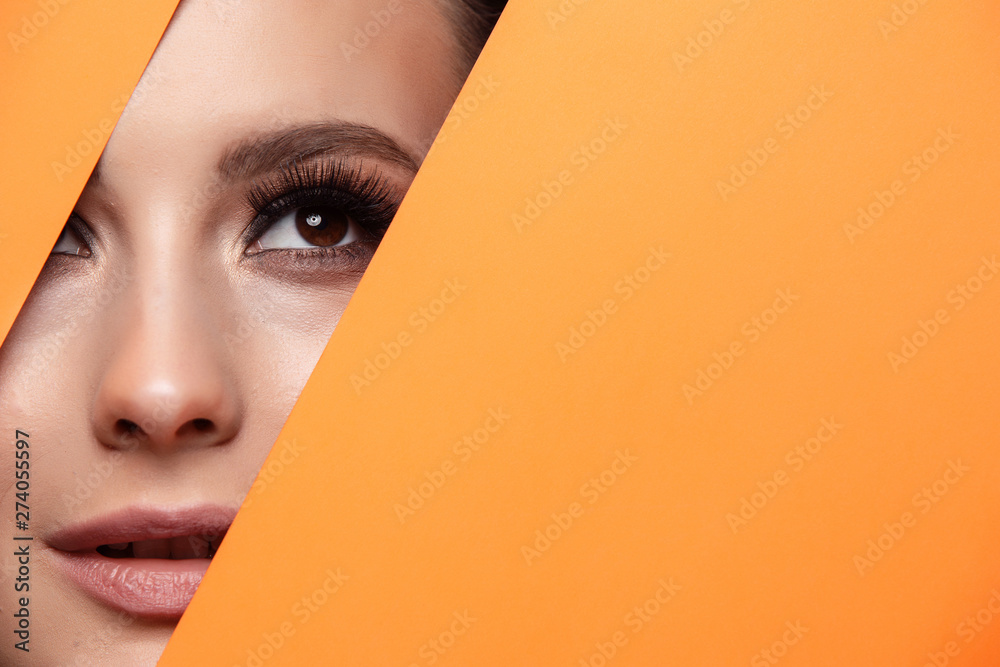 Fototapety, obrazy: A girl with beautiful curry bright beautiful eyes with brown shadows and expressive eyebrows looks into the hole of colored paper.Fashion, beauty, make-up, cosmetics, make-up artist, beauty salon,busi
