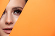 Leinwandbild Motiv A girl with beautiful curry bright beautiful eyes with brown shadows and expressive eyebrows looks into the hole of colored paper.Fashion, beauty, make-up, cosmetics, make-up artist, beauty salon,busi