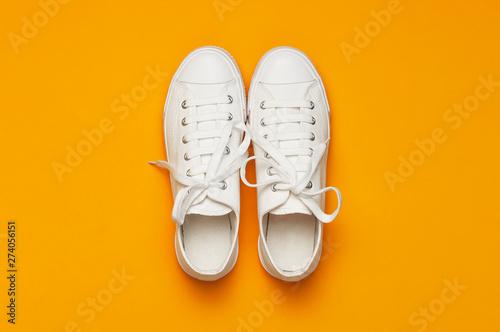 Cuadros en Lienzo  White female fashion sneakers on yellow orange background