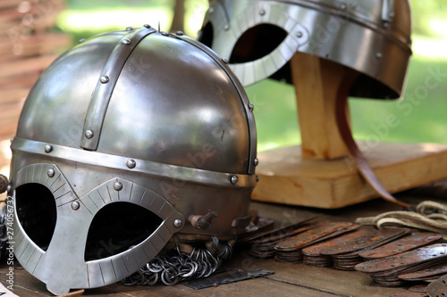 Aluminium Prints Scooter Medieval helmets on a wooden table. Armor of middle ages, knightly equipment, armory forge background
