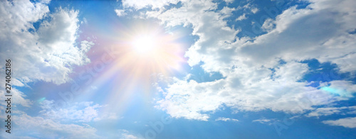 Glorious Sunlight Breaking through the Clouds - wide sky banner with big fluffy clouds and a bright sun bursting through with room for copy