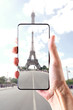 view on the Tour Eiffel: male hand holding a smartphone frame the Tower