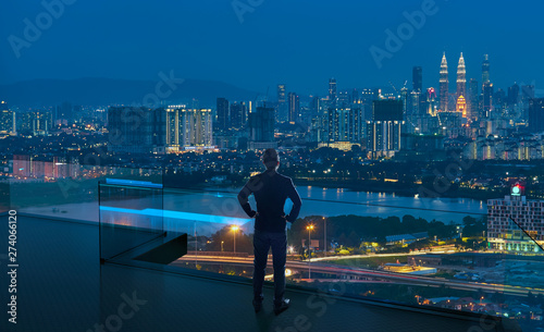 Obraz Businessman standing on open roof top balcony watching city night view . Business ambition and vision concept . - fototapety do salonu