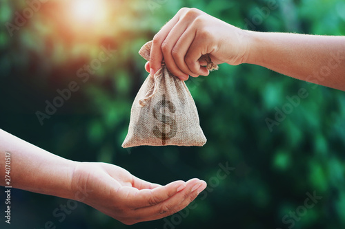 Fototapeta hand giving money bag to another people on green background with sunrise obraz