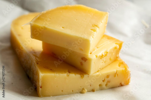 Fototapeta Piece of cow cheese with fenugreek seeds made in Belgian abbey by monks. obraz