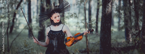 panoramic view of woman in witch costume with crown standing on forest background, holding violin - 274076118