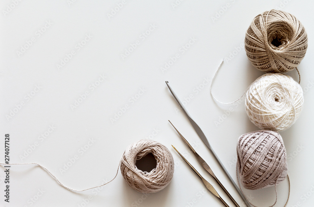 Fototapety, obrazy: Needlework. Crochet hooks and balls of cotton yarn beige color on a white table. Тоp view, closeup, flat lay, copy space