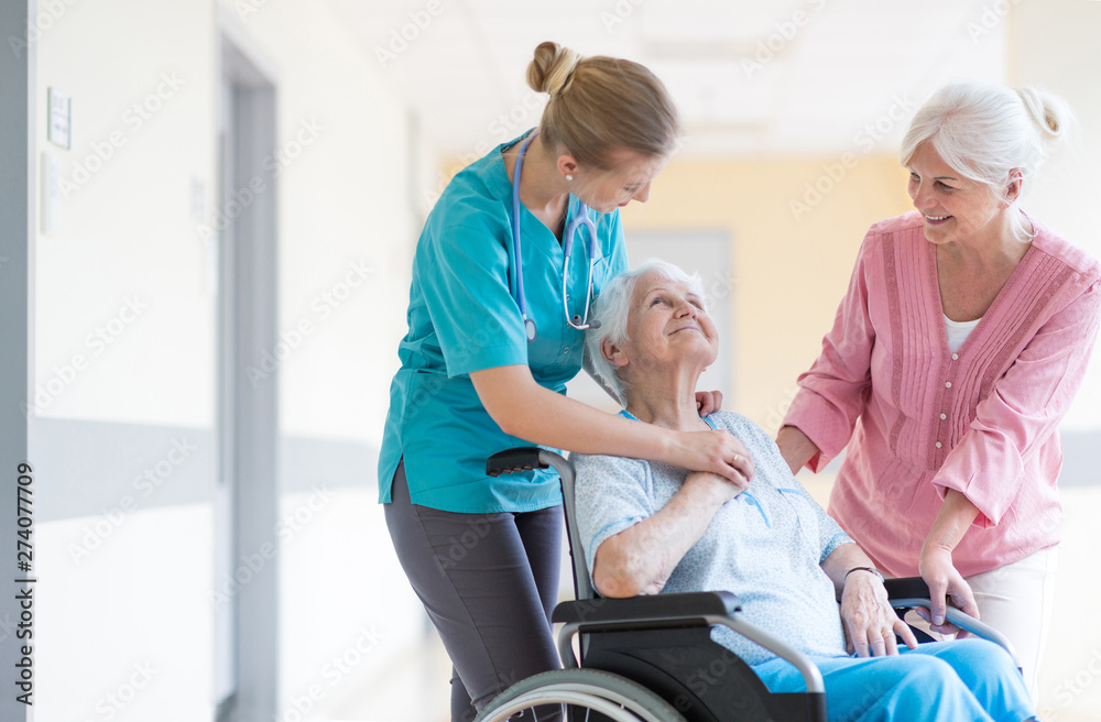 Fototapety, obrazy: Elderly woman on wheelchair with her daughter and nurse