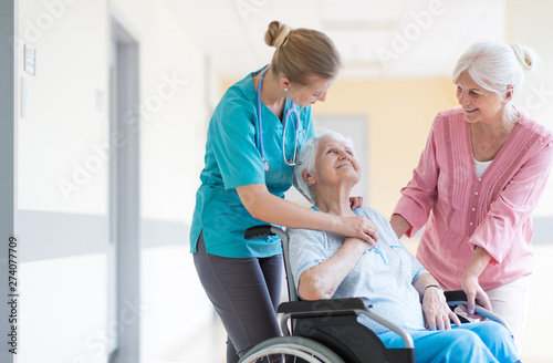 Fotomural  Elderly woman on wheelchair with her daughter and nurse
